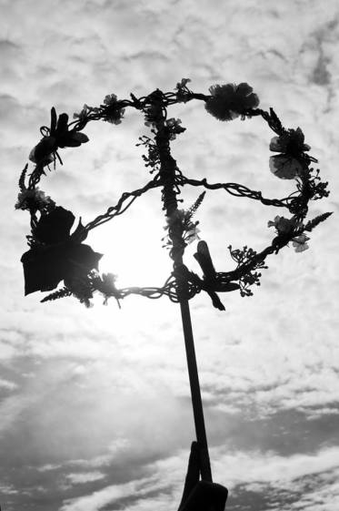 Black and white photo shows peace sign made of flowers