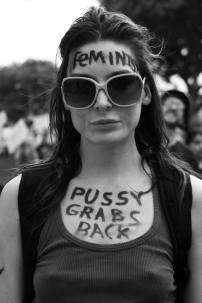 """Woman is shown with the word """"Feminist"""" written on her forehead and the words, """"Pussy grabs back"""" written along her chest"""