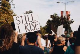 """Trump protesters march, one man holds a sign reading, """"Still I rise"""""""