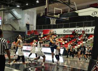 Opposing team baketball player shoots to score a basket