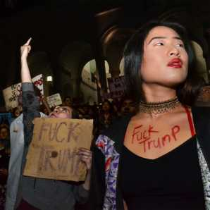 """Two women are shown with body art and signs reading """"Fuck Trump"""""""