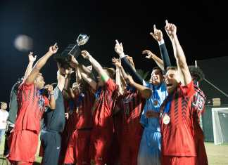 Team cheers and holds up trophy