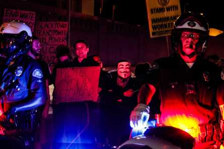 Protesters shown standing behind several police men