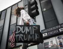 """Protester is standing on traffic light carrying a American flag in a briefcase that says, """"Dump Trump"""""""
