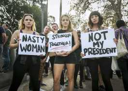 """Three protesters hold signs reading, """"Nasty Woman"""", """"Stronger Together"""" and """"Not My President"""""""
