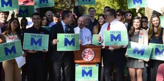 "A group of people pose with signs that say, ""yes on M"""