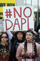 """Woman at protest holds sign that says, """"# no D.A.P.L."""""""