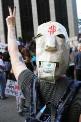Woman pictured at protest with a hat that looks like a face eating money