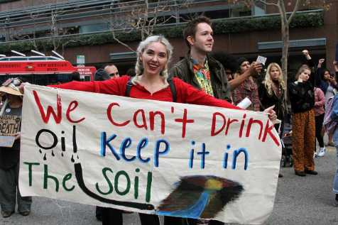 """Woman holds sign that says, """"we can't drink oil, keep it in the soil"""""""