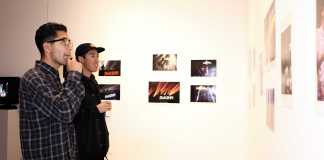 Students look at photographs on the wall