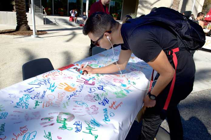 Student signs his name on a table cloth