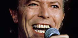 Photo of a young David Bowie holding a microphone