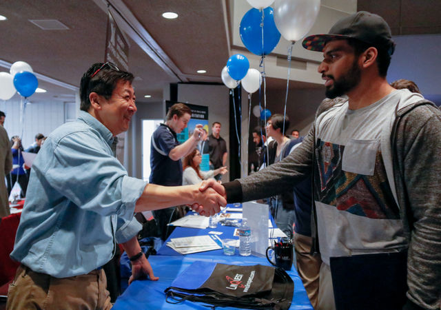Christopher Whang shakes hands with a student at tech fest