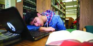 Photo shows a student napping in the library