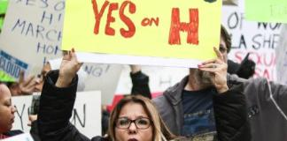 """woman protests with poser that reads, """"nobody deserves to live on the streets yes on H"""""""