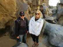 two students pictured surrounded by large rock structure