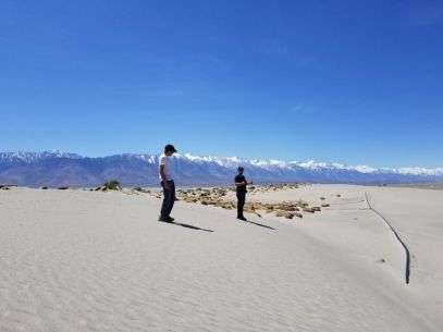 students pictured standing on a large mound of sand surrounded by mountains