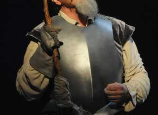 Man wears armor along with some fake facial hair to play Don Quixote