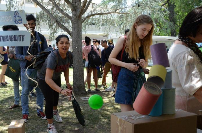 student plays a carnival game at earth fair