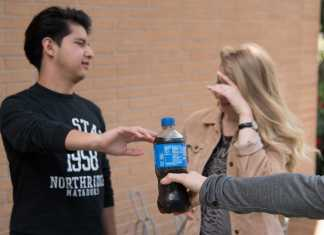 two students pictured refusing a bottle of pepsi
