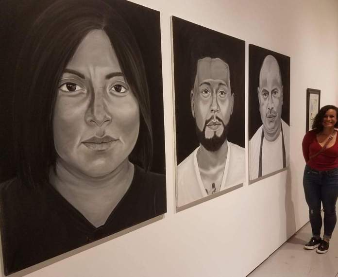 Hedy Torres poses next to her artwork