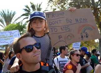 "Little girl sits on her dad's shoulders at protest with a sign that says, ""Trump don't be mean to kids"""