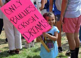 "young girl (no older than 4) holds up a sign that says, ""only bullies crush dreams"""
