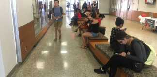 Photo shows several students sitting on the benches located on the first floor of sierra hall
