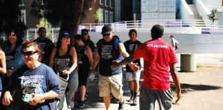 volunteer in red shirt supporting walkers in black shirts
