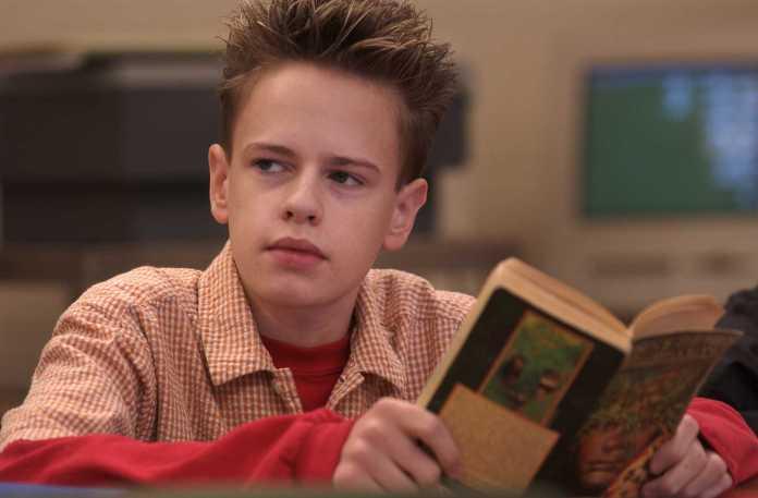 boy in orange and white collard shirt holding a book