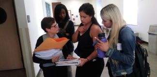 three female students speak to professor in white hallway