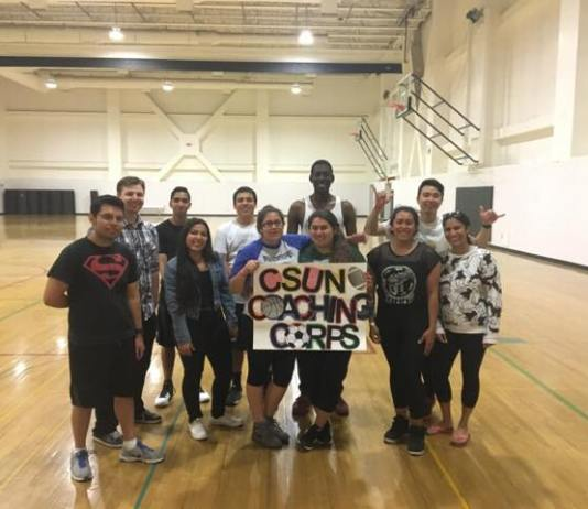 men and woman holding a sign reading CSUN Coaching Corps