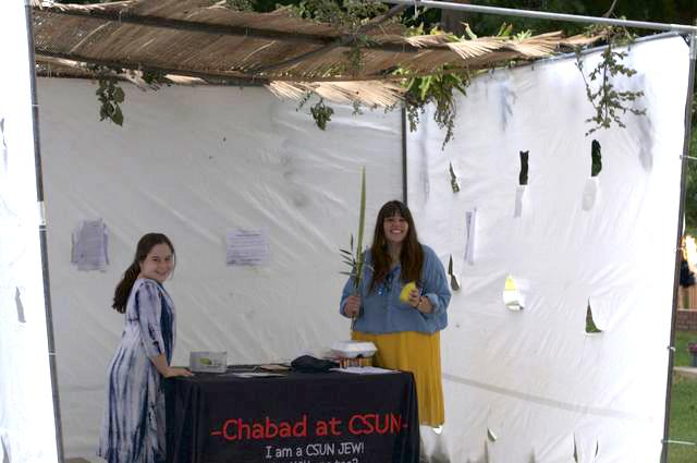 young girl and woman smiling standing behind black table that reads Chabad at CSUN in red