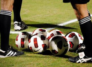 soccer balls on field with referees surrounding them