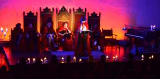 woman sit in large red cloaks on stage