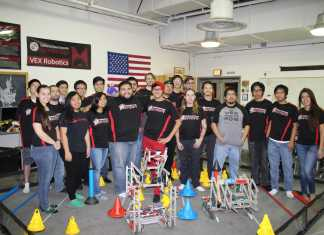 Students in uniformed shirts happily pose for a photo with their robots