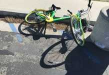 green and yellow limebike on the floor next to the curb