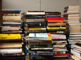 Multiple large stacks of books on a desk.