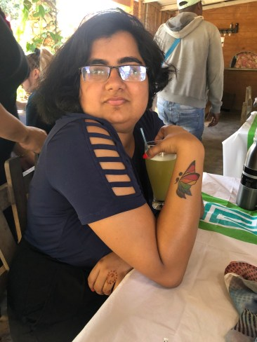 A brown femme person with shoulder length black har sitting at a table. They have a drink in their hand and a butterfly tattoo in pride colors is visible on their wrist.