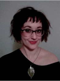 White woman with dark hair and glasses smiling slightly at camera, wearing an off-the-shoulder navy blouse and large necklace with silver leaf