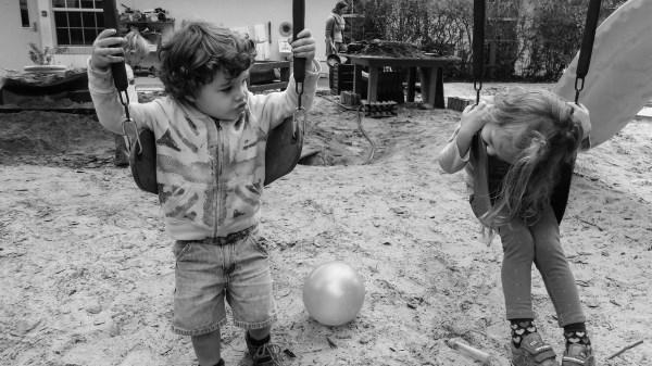 two kids on a swingset