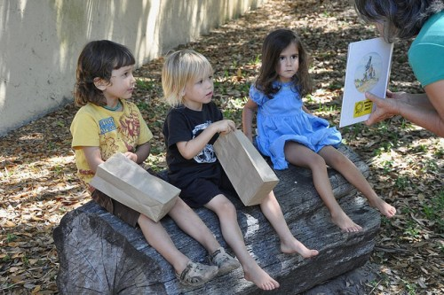 children sitting on a log listening to a book