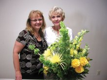 Barbara Renee Oliver, owner of Flowers by Renee (left) is pictured with the beautiful arrangement she designed and Sun Lakes Garden Club member Jana Matousek, who won it.