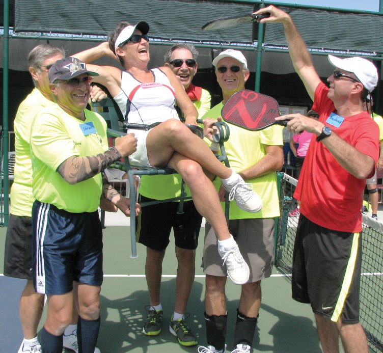 Tom Kasper, David Novikoff, Rich Nadler and David Zapatka carry Cleopatra (JoAnn Zapatka) on her throne to her next match as Mike Mann keeps her cool by fanning her with pickleball paddle fronds!
