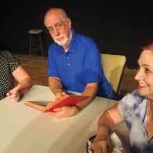 Raynelle (Andrea Hummel), Reverend Hooker (John Crawford) and Delightful (Joan Berger) attempt to come up with a suitable eulogy for Raynelle's late husband, Bud.
