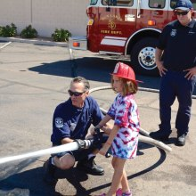 "Firefighter Craig Daniels lets this young girl get a chance to put out the ""fire."" Firefighter Brandon Johnson watches."