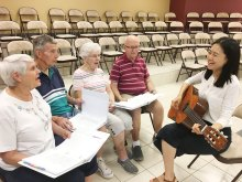 Director Sun Joo Lee works with Sun Lakes residents Don and Toni Kalschevr and Harry and Helen Folkvord.