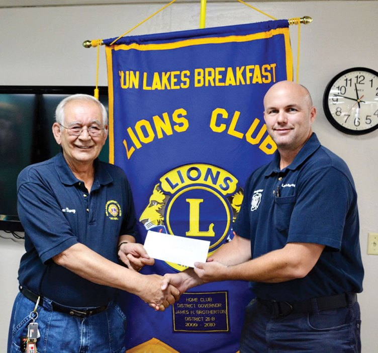 "Sun Lakes firefighter and union (IAFF Local 3560) Vice President Les Pechacek accepts a check from Mac Davey for the union's ""SLERF"" fund."