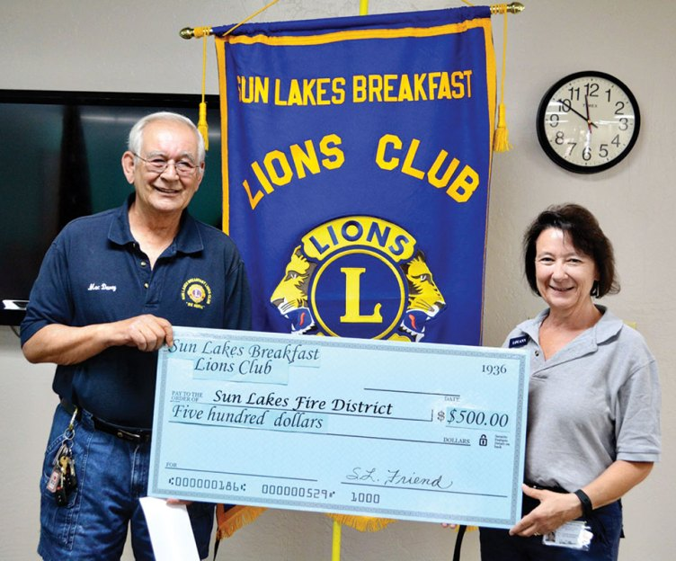 "LouAnn Sedgwick, an Executive Board member of the Sun Lakes fire district's CAP (Community Assistance Program), accepts a ""check"" from Mac Davey."
