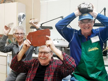 "Rocks in their heads: Outgoing Lapidary Chair Mike Stegina (seated front) displays a Red Jasper rock find from ""not far away"" (we don't give away secret hunting grounds). Gail Wilder is one of our Lapidary instructors, and Bob Walstad just loves rocks."